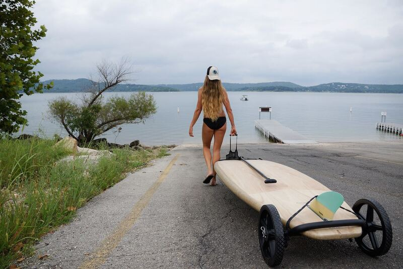 Girl walking SUP Wheels and SUP board to water